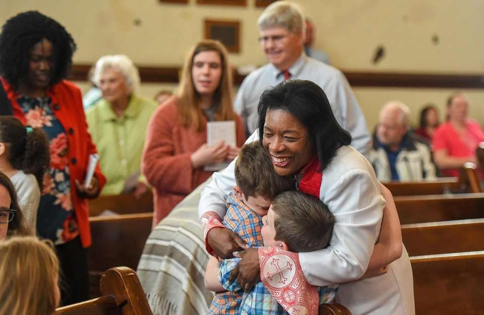 Rev. Wendy Modeste hugs Tyler Seyda, 10, left,