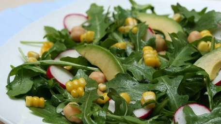 Arugula salad with corn and radishes is made