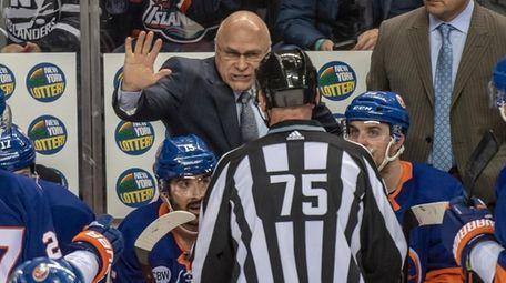 Islanders head coach Barry Trotz talking with referee