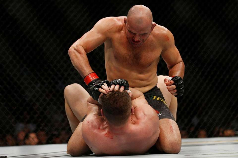 Glover Teixeira of Brazil punches Ion Cutelaba of