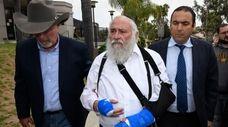 Rabbi Yisroel Goldstein, center, arrives for a news