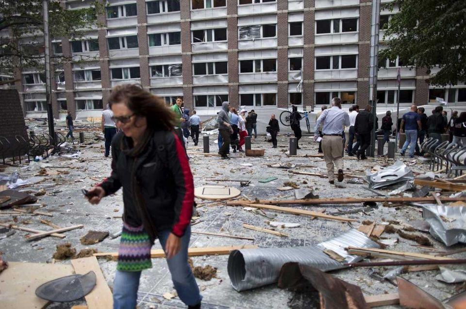 A woman walks through debris in a street