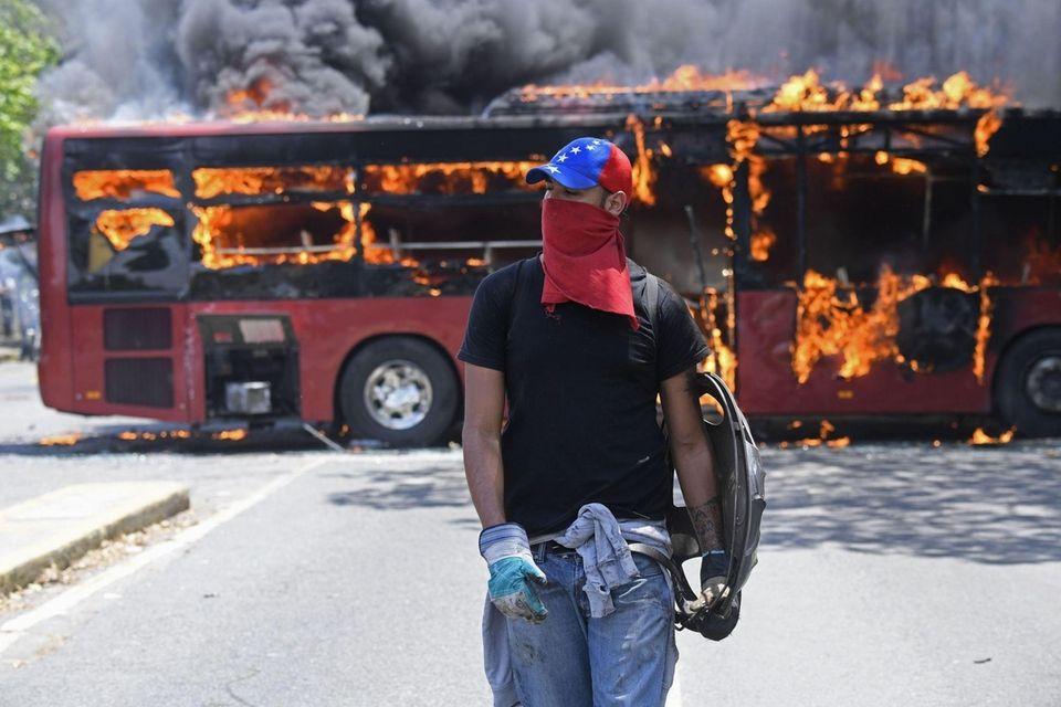 An opposition demonstrator walks near a bus in