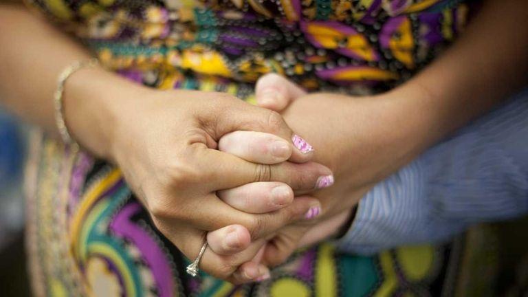Robin Weinrib holds Lauren Ernst's hand as they