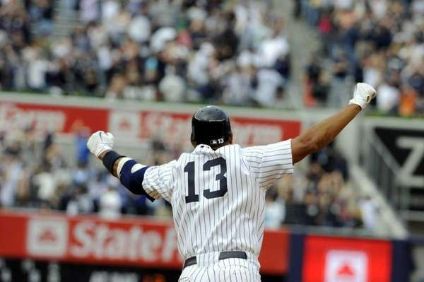 Alex Rodriguez raises his arms after hitting the