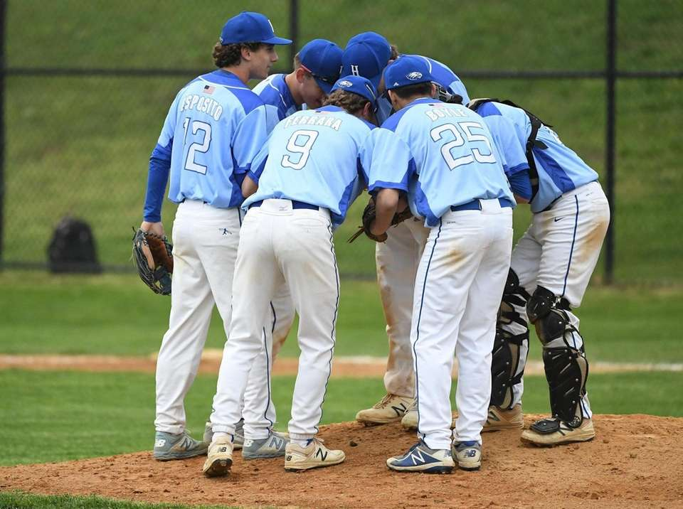 Hauppauge players huddle on the mound during a