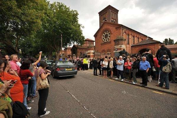 Mourners gather outside the ceremony held for Amy