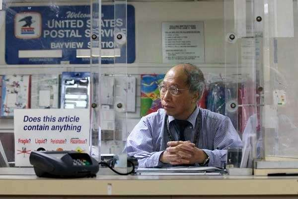 U.S. Postal clerk Shun Wong waits for customers