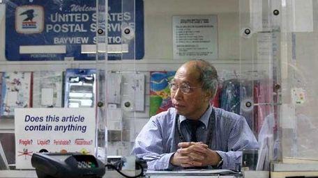 U.S. Postal clerk Shun Wong waits for customers
