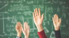 Students raised up hands green chalk board in