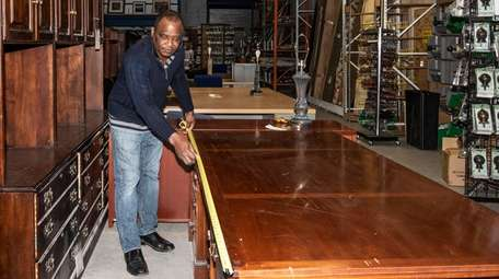 Ajax Thimote of Uniondale measures a desk at