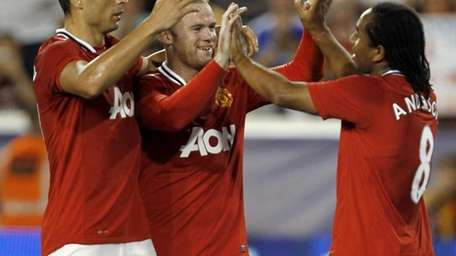 Manchester United's Anderson, right, is congratulated by teammates