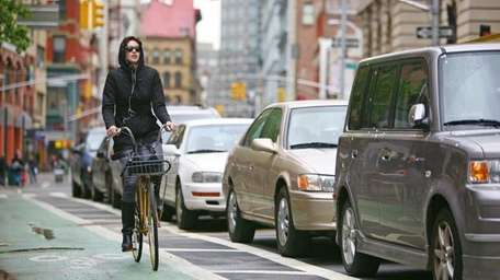 A bicyclist makes her way east on the