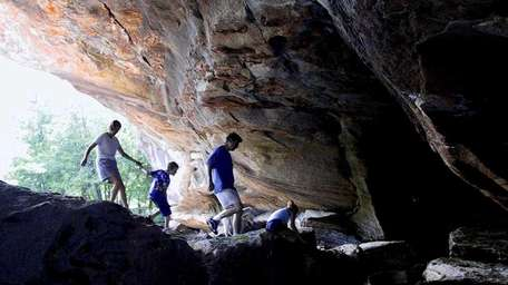 A family enters the large marble cave entrance