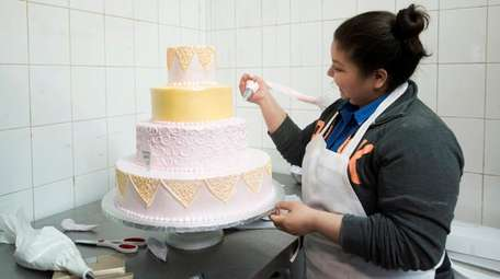 A Francesco's Bakery employee puts the finishing touches