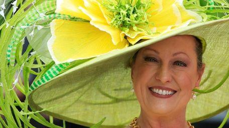 A woman wearing a festive hat looks on