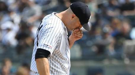 Yankees starting pitcher J.A. Happ reacts after giving