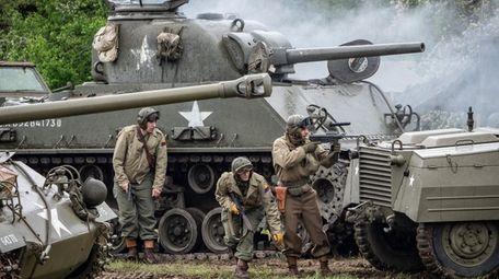 Re-enactors wearing World War II uniforms portray American