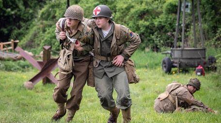 Reenactors wearing World War II uniform reenact a