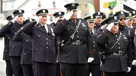 Law enforcement officers salute during the Fraternal Order