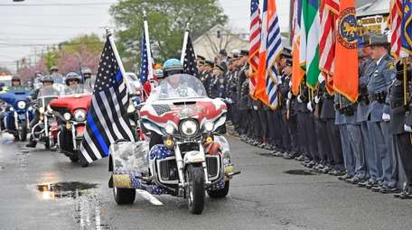 A procession of motorcycles rolls past the assembled