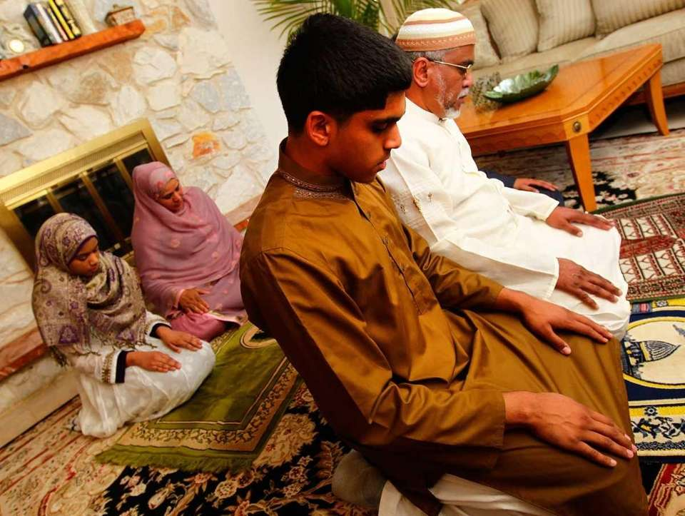 The Imam family preys at their home in