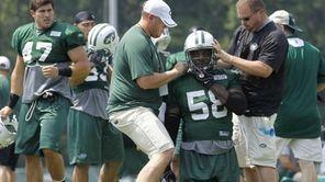 New York Jets linebacker Bryan Thomas gets help