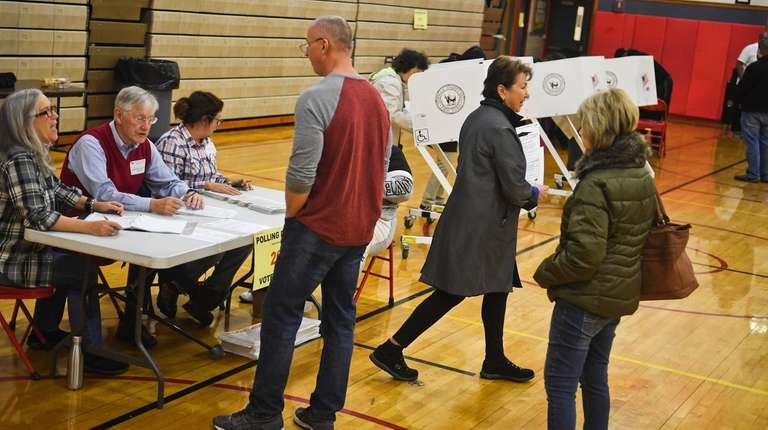 Voting inspectors assist voters on Election Day at