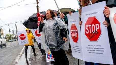 Protesters gather on a rainy Sunday outside the