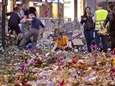 Workers remove flowers and candles, placed in front
