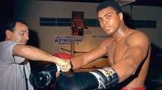 Muhammad Ali gets his gloves laced by trainer