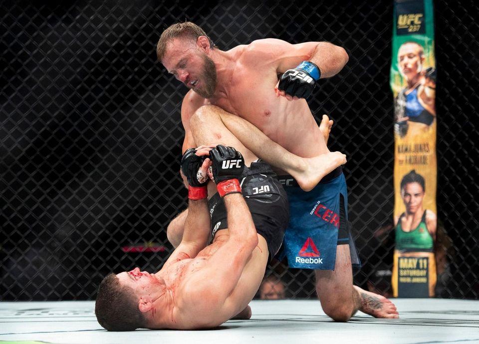Donald Cerrone, top, punches Al Iaquinta during a