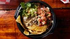 The pernil bowl features shavings of pork over