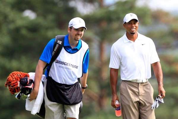 Tiger Woods (R) walks up the 11th fairway