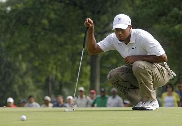 Tiger Woods looks over a birdie putt on