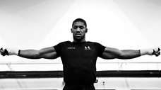 Anthony Joshua stretches during a training session during