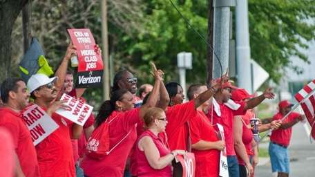 Verizon employees yell across the street at non-striking