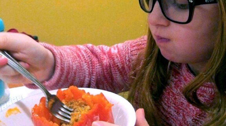 Caitlyn Wilbert eating a stuffed pepper.