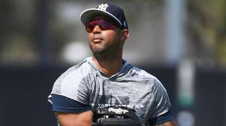 Yankees centerfielder Aaron Hicks warms up during spring