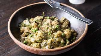 Gnocchi is tightly dressed with dandelion pesto, spring