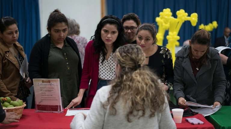 Job seekers speak with a recruiter during a