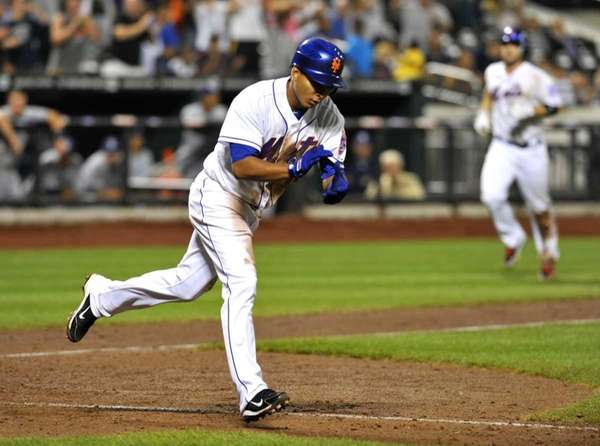 Ruben Tejada claps as he trots to first