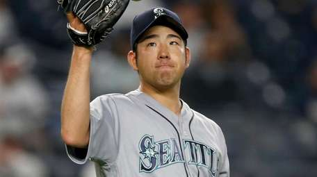 Yusei Kikuchi of the Mariners reacts after giving