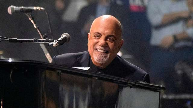 Billy Joel smiles at a fan as he