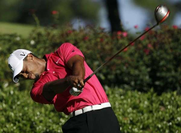 Tiger Woods hits a drive on the 12th