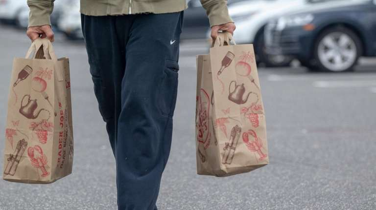 A shopper walks with paper bags outside Trader