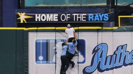 Security chases a fan of the Tampa Bay