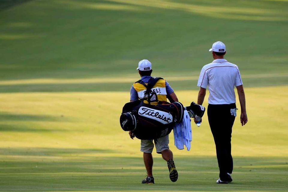 Brendan Steele walks with his caddie Nick Wilkins