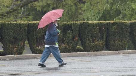 A man walks with an umbrella in Selden