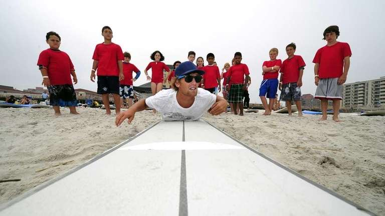 Surfing instructor Will Skudin shows young students how